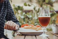 A Person Drinking Beer And Eating A Hotdog Royalty Free Stock Images
