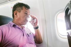 Person drinking water in airplane long haul flight to hydrate Royalty Free Stock Images
