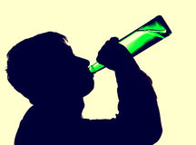 Person drinks a Beer. Toned Photo of Young Man Silhouette with a Beer Bottle Stock Photo