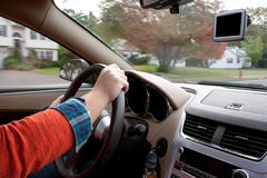 Person Driving a Car. A woman holds the steering wheel of a car while driving down the road Stock Photos
