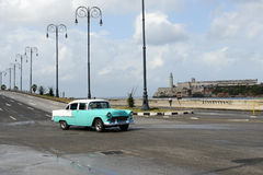 Person driving his vintage car at the Malecon in Havana. Havana, Cuba - 27 January 2016: Person driving his vintage car at the Malecon in Havana on Cuba Stock Photo
