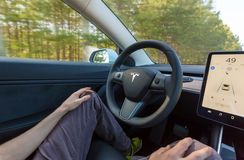 Person driving a new Tesla Model 3 in autopilot mode. stock photo