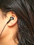 Person with ear plug. A person with an ear plug for music, and mobile hands-free, with wire royalty free stock image