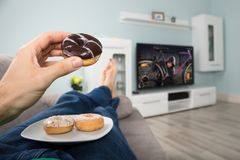 Person Eating Donut While Watching-Televisie royalty-vrije stock foto