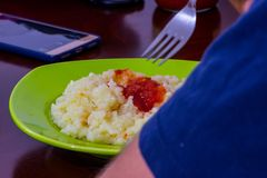 Person eating home made food at break time. Lonely person eating the rice with tomato sos at his break time Royalty Free Stock Photo