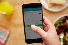 Person Eating Lunch Looking At-Geschiktheid App op Mobiele Telefoon royalty-vrije stock foto