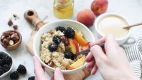 Person eating oatmeal porridge, healthy breakfast