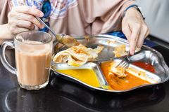 Person eating roti prata or canai with curry and dhal stock image