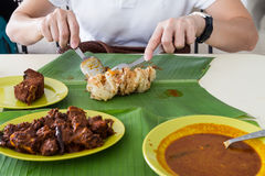 Person eating roti prata, masala mutton, fish on banana leaf Royalty Free Stock Image