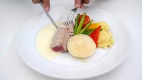 A person eating tuna steak as main dish. Tuna Steak Gourmet. A person eating tuna steak as main dish stock video