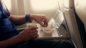 Person eats breakfast in old plane economy class stock video