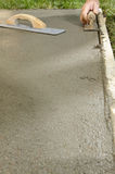 Person edging wet cement slab with concreting tool. A person carefully edging a wet cement slab during the finishing stages of a backyard, DIY concreting project Royalty Free Stock Photos