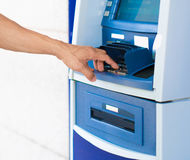 A person entering a pin number at a blue ATM machine. Blue ATM machine. Closesup of hand pushing buttons Stock Photo