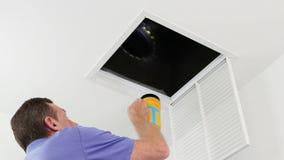 Person Examining HVAC-kanal med en ficklampa lager videofilmer