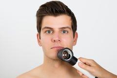 Person Examining Man Face With Dermatoscope Imagen de archivo