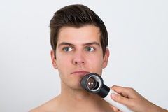 Person Examining Man Face With Dermatoscope Imagenes de archivo