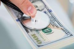 Person examining money with stethoscope Stock Photo