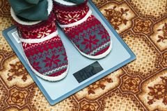 Person feet in new year shoes standing on weight scales royalty free stock photography