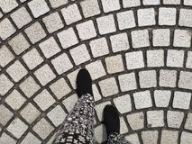 A person feet ware black shoes walking on grey cobblestone curve pattern paving on a street. A person feet ware black shoes walking on grey cobblestone  curve stock photo