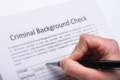 Person Filling Criminal Background Check Form. Close-up Of A Person`s Hand Filling Criminal Background Check Form With Pen stock photos