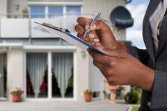 Person Filling Document In Front av huset royaltyfria foton