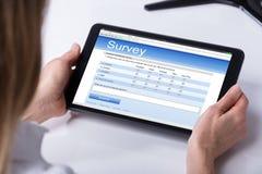 Person Filling Online Survey Form en la tableta de Digitaces fotografía de archivo libre de regalías