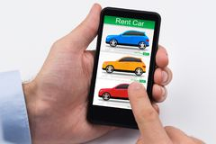 Person Holding Cellphone With Colorful Cars On Screen royalty free stock images
