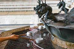 Person filling up ladle with water of chozuya fountain. Traditional Japanese Shinto washbasing for ritual cleansing of worshippers at the entrance to holy Royalty Free Stock Photo