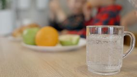 Person fills glass with water against kids in room and fruits on. Process of fills glass with water. Bottle and small cup or mug standing on the wooden table stock footage