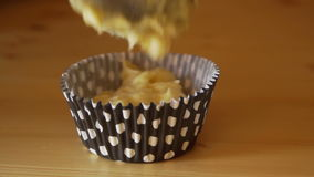 Person fills out a black polka dot cupcake tins with dough stock footage