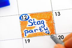 Person fingers with pen reminder Stag Party in calendar. Royalty Free Stock Photography