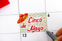 Person fingers with pen writing reminder Cinco de Mayo in calendar stock photos
