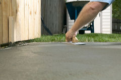 Person finishing wet cement with concrete screed. A person finishing wet cement with a concrete screed in a backyard, DIY home project themed image Royalty Free Stock Photo