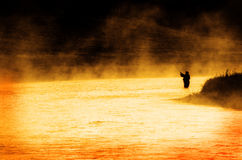 Person Fishing Man Silhouette Sunrise River Lake Mist. Man fishing in river or lake silhouette by sunrise and misty water Royalty Free Stock Images