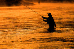 Person Fishing Man Silhouette Sunrise River Lake Mist. Man fishing in river or lake silhouette by sunrise and misty water Stock Images