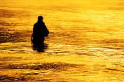 Person Fishing Man Silhouette Sunrise River Lake Mist. Man fishing in river or lake silhouette by sunrise and misty water Royalty Free Stock Photos