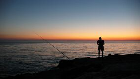 Person Fishing during Sunset Stock Images