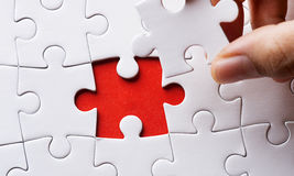 Person fitting the last puzzle piece Royalty Free Stock Images