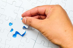 Person fitting the last puzzle piece Stock Image
