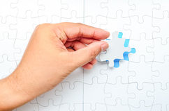Person fitting the last puzzle piece. Concept image of building and button up Stock Photography