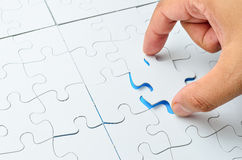 Person fitting the last puzzle piece Royalty Free Stock Photo