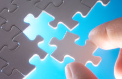 A person fitting puzzle pieces on blue background. Royalty Free Stock Photos