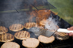 Person Flipping Burgers During BBQ Royalty Free Stock Images