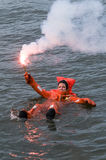 Person floating in survival suit holding red handflare Stock Image
