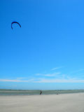 Person flying kite on beach. Person flying kite on sandy beach with blue sky background Stock Image