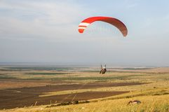 Person flying on paraplane. Sky with clouds on background Royalty Free Stock Photography