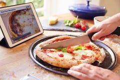 Person Following Pizza Recipe Using-APP auf Digital-Tablet Stockfotos