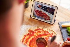 Person Following Pizza Recipe Using App på den Digital minnestavlan Royaltyfri Foto