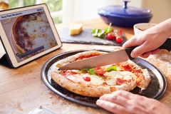 Person Following Pizza Recipe Using APP sur la Tablette de Digital Photos stock