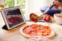 Person Following Pizza Recipe Using APP sur la Tablette de Digital Image libre de droits